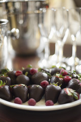 Wedding dessert. Plate of hand-dipped organic strawberries, fruit in artisinal handmade chocolate with raspberry garnish.