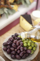 A dish of fresh organic vegetables. Green and black olives on a plate with a drizzling of olive oil from a bottle. Prepared farmstand foods for a party