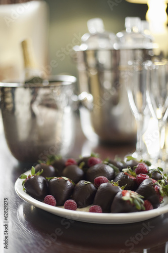 Wedding dessert. Plate of hand-dipped organic strawberries, fruit in artisinal handmade chocolate with raspberry garnish. Champagne and glasses.