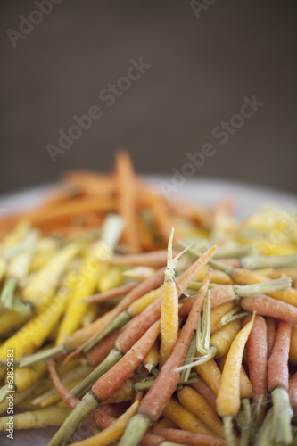 Organic vegetables in a dish. Cooked orange, yellow and pink heritage baby carrots. Farmstand produce.