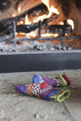 A log fire in a hearth with glowing heart, and flames. Patterned knitted woollen gloves.