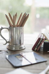 A tabletop with a silver tankard full of colouring crayons. Gift wrapped packages.