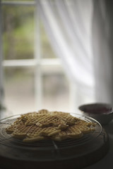 A dish of waffles on a tabletop. Net curtains draped back from a window.