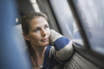 A woman sitting at a window seat in a train carriage, resting her head on her hand. Looking into the distance.