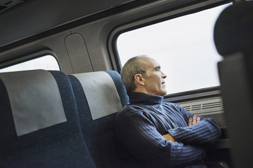 A mature man sitting in a window seat on a train journey, looking out into the distance.