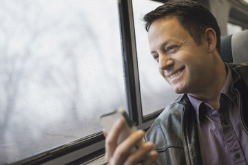 A mature man sitting at a window seat on a train, holding his mobile phone. Smiling and looking in the distance.
