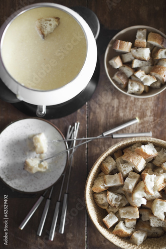 A cheese fondue on a table top. Cubed bread and long forks, for dipping bread into rich melted cheese mixture.
