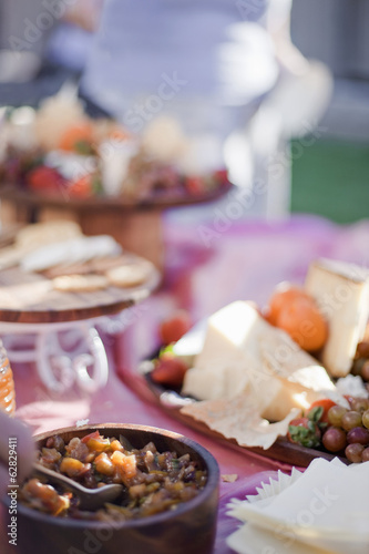 A table laid with a buffet selection of food dishes.  Desserts and cheese board.
