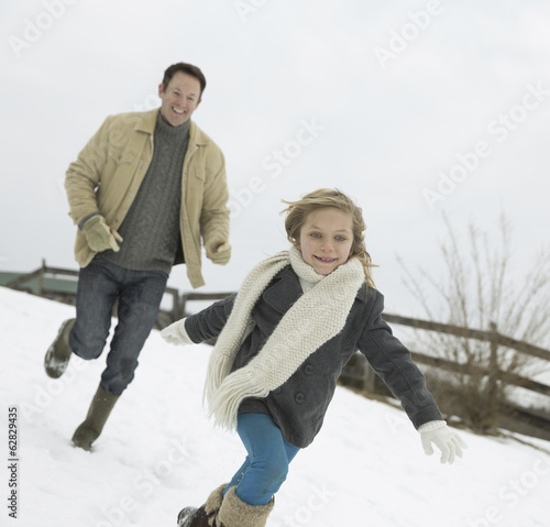 A man chasing a young girl in the snow.  Farm in winter.