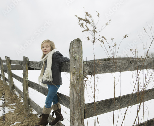 A farm in the snow.  A girl with a hat and scarf and boots, leaning on a fence.