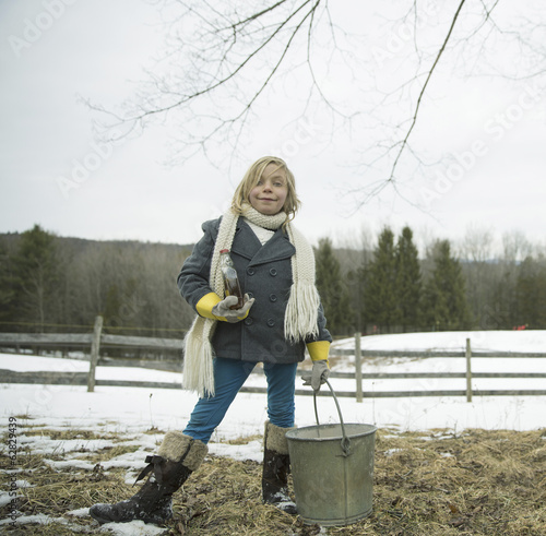 A girl in the snow, carrying a metal bucket.