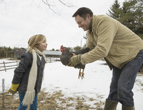A man holding a chicken in his hands. A girl leaning forwards. Farm in the snow.