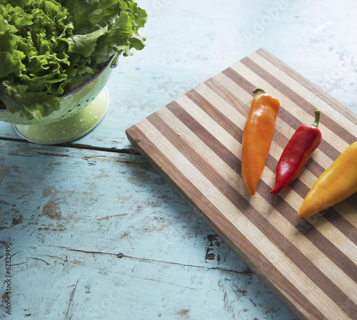 A tabletop with a wooden chopping board and three sweet peppers, and a bowl of salad leaves.