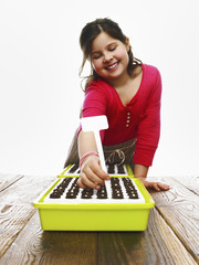 A young girl planting seeds in a modular seed tray with dark organic soil.