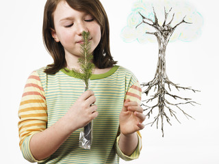 A young girl holding a small evergreen seedling to her nose and smelling it. An illustration of the plant with roots on a clear seethrough surface.