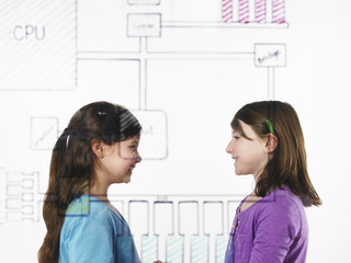 Two children facing each other behind a drawing of a computer motherboard circuit drawn on a see through clear surface.