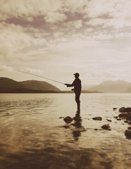 Silhouette of a man flyfishing in calm waters on the Waschusett inlet in Glacier Bay national park in Alaska.