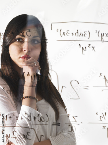 A young woman looking at a mathematical equation written out with black marker on a clear seethrough wall.