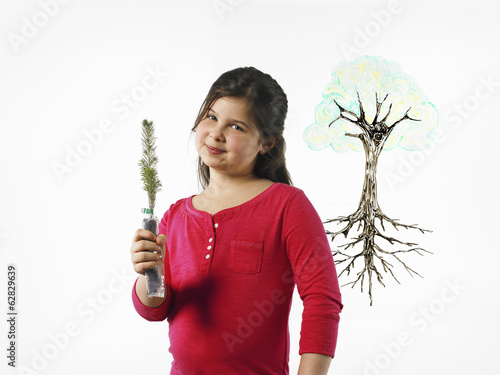 A young girl holding a small evergreen seedling. An illustration of a plant with roots drawn on a clear surface.