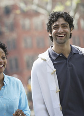 People outdoors in the city in spring time. New York City park. A man and woman side by side, smiling.