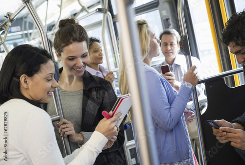 New York City park. People, men and women on a city bus. Public transport. Two women looking at a handheld digital tablet.