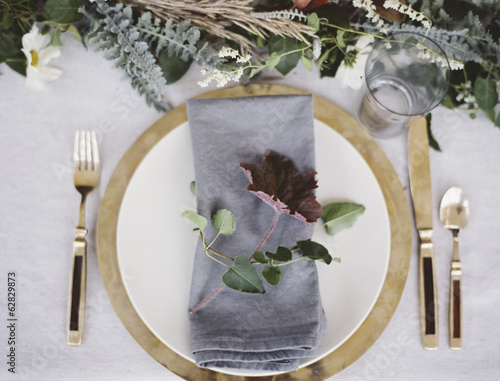 A table top covered with  a white cloth. A place setting with cutlery and plate. A napkin and a foliage table decoration.