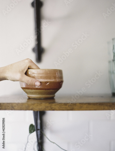 Farm to Table. A person reaching up for a pottery bowl in a domestic kitchen.