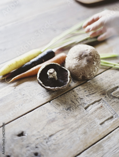 A domestic kitchen table with a worn scrubbed surface. A bunch of carrots, and mushrooms. Fresh vegetables.