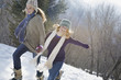 Winter scenery with snow on the ground. A woman and a child hand in hand running across the snow.