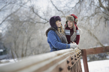 Winter scenery with snow on the ground. A couple, young man and young woman, leaning on a fence.