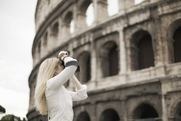 A woman outside the Colosseum amphitheatre in Rome, taking photographs.
