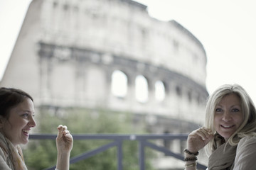 Two women seated on a terrace overlooking the huge Roman amphitheatre building, the Colosseum in Rome.