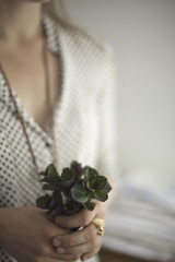 A woman wearing a dress and necklace, holding a small bunch of red and green plant leaves. Cologne mint leaves.