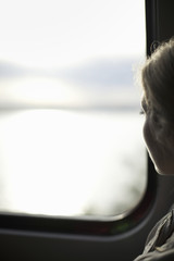 A woman sitting by a train window looking out at the view.