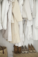 A closet with cream and white clothes, jackets, shirts and tunics hanging up. A row of women's shoes arranged neatly on the floor.