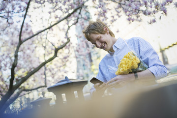 City life. A young man in the park in spring, using a mobile phone.  Holding a bunch of yellow roses.