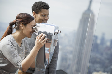 New York City. An observation deck overlooking the Empire State Building. A young couple looking through the telescope.