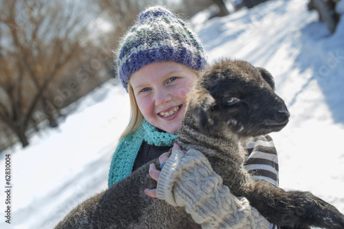 Winter scenery with snow on the ground. A young girl holding a young lamb.