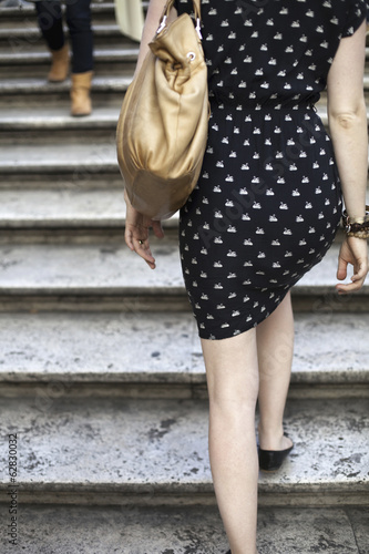 Back view of a young woman wearing a blue and white patterned dress and carrying a large handbag. Climbing up marble steps in Rome.