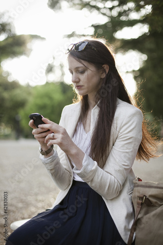A woman wearing a cream jacket, sitting in a city park looking at her cell phone.