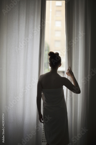 A young woman with her hair up, wearing a bath towel, looking through long curtains at a window.