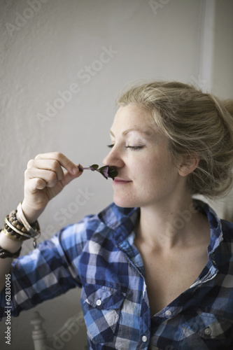 A young woman with blonde hair, holding a aromatic plant or herb flower to her nose and inhaling the aroma.