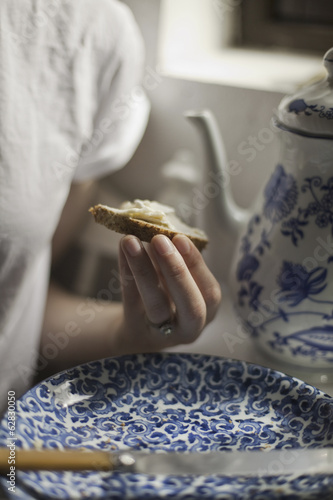 A breakfast table with a tall coffeepot and blue and white china plate. A woman sitting holding a piece of buttered bread.