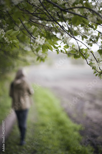 A woman in a brown hooded coat and hat walking along a path beside a ploughed field.