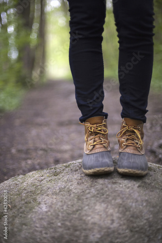 A woman wearing walking boots and jeans, standing on a stone beside a path in woodland.