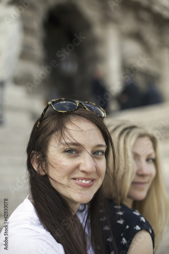 Two women in the street in the historic city of Rome. A blonde haired woman and a brunette.