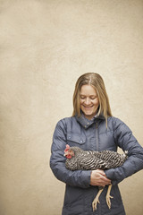 A woman wearing a grey coat and holding a chicken.