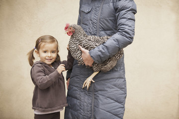 A woman in a grey coat holding a black and white chicken with a red coxcomb under one arm. A young girl beside her holding her other hand