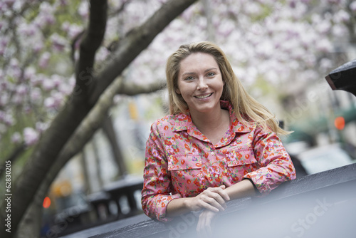 City life in spring. A young woman with long blonde hair, outdoors in a city park.