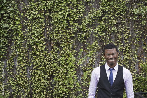 City life in spring. City park with a wall covered in climbing plants and ivy.  A young man in a waistcoat, shirt and tie. Looking at the camera.
